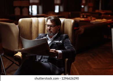 Adult man in his fifties, successful entrepreneur in spectacles and suit reading newspaper while sitting in luxury genuine leather arm-chair in dark room with lighted lamps