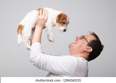 Adult man hold his with terrier puppy above.