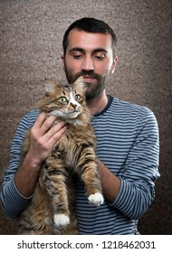 Adult man holding Norwegian forest cat.