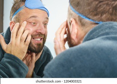 Adult man investigating his wrinkles on face. Guy after waking up looking at himself in mirror. Aging process concept.