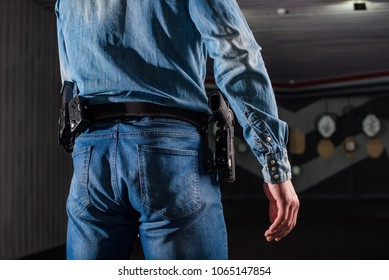 An adult man in jeans trains to shoot a gun in a closed dash.