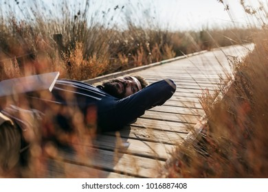 Adult man with laptop chilling on wooden pier in tall grass and enjoying freedom in sunlight.