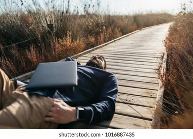 Adult man with laptop lying on wooden pathway in rural field dreaming happily in sunlight.