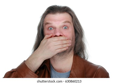 An adult man with long hair in surprise covers his mouth with his hands, white isolated, copyspace.