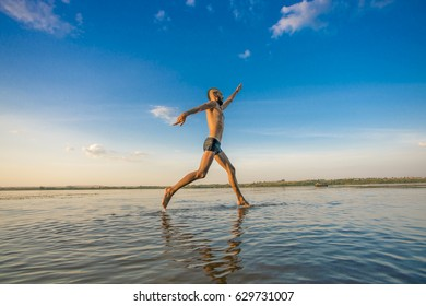 Adult man with a mohawk on his head and black shorts running on water against the backdrop of blue sky with clouds