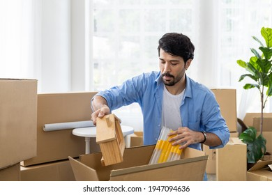 Adult man with mustache and beard packaging cardboard boxes for moving into a new house