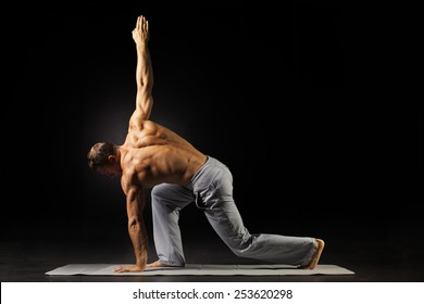 adult man with naked torso doing exercise on black background