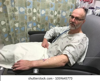 Adult man on medication intravenous in hospital clinic receiving medical care