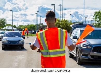 Adult man in an orange safety vest, medical face mask, blue gloves, with a red flag, regulating car traffic movement. Back view.