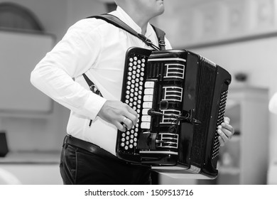 Adult man plays the button accordion