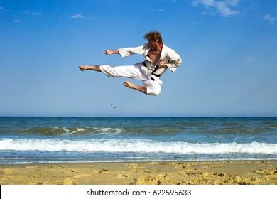 Adult man practicing a kata and kicks on the beach. Karateka jumping against the sea.