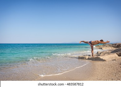 Adult man practicing yoga on the beach in Greece, in position warrior three