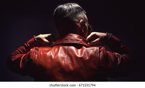 Adult man in red leather jacket, view from back.
