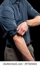 Adult man rolling up his sleeves. Studio shot over black.