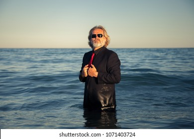 Adult man in the sea with a black suit and a red tie