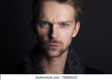 Adult man with serious face in front of dark background