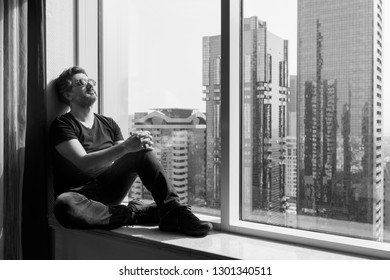 Adult man sitting by window in skyscaper.