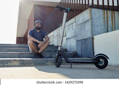 adult man sitting in front of his electric scooter, with beard and helmet