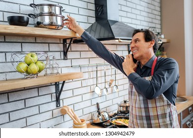 Adult man stand in kitchen and talk on phone. He reach hand to pan. Guy wear apron. He stand alone.
