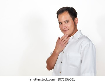Adult man standing with his hand on his chin wearing a white shirt isolated on white