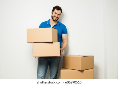 adult man standing next to a stack of carton boxes on white wall