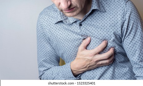 Adult man suffering from severe sharp heartache, chest pain. Heart disease concept