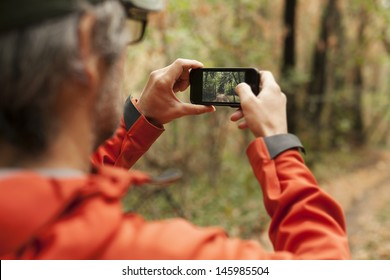 Adult man taking a picture with smart phone. Outdoor shot in nature. Shallow depth of field.