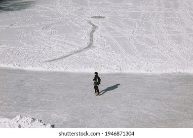An adult man, a tourist walks through the fresh snow and slippery ice in black clothes in the winter, exploring the country. Photography, copy space.