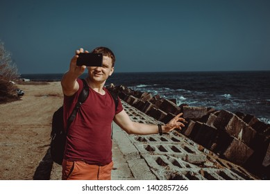 Adult man travel the world. Happy and confident businessman taking selfie on vacation. Tourist with smartphone. Tourism concept. Odessa seaview. Explore Ukraine. Black Sea background. Copy space