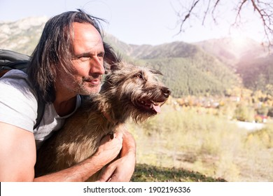 An adult man travels with a dog. They are together in the mountains.