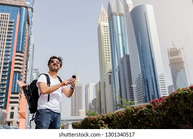 Adult man using mobile phone in city street.