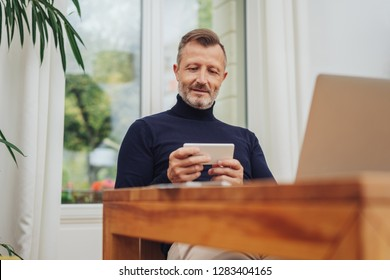 Adult man using smartphone in landscape mode, looking at the screen and smiling, while sitting at the table at home. Front portrait from low angle, against the window