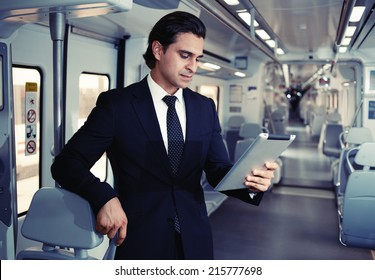 Adult man is using a Tablet PC, businessman working with tablet on the way to work, businessman holding digital tablet pc, businessman uses the new media technologies and devices to work successfully