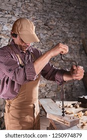 Adult man wearing light brown work overalls using long drill to put hole in wooden beam sitting on table