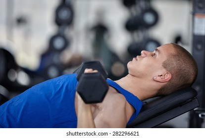 Adult man with weight training equipment on sport modern gym