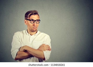 Adult man in white shirt and glasses holding hands crossed and looking grumpy being jealous and envy