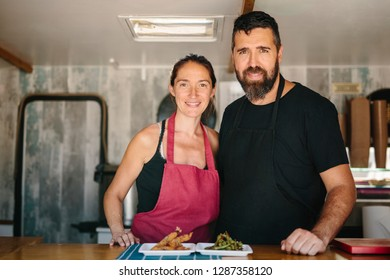 Adult man and woman in aprons standing in food truck smiling at camera