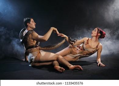 Adult man and woman like Adam and Eve together with tiger python snake isolated on black background in studio