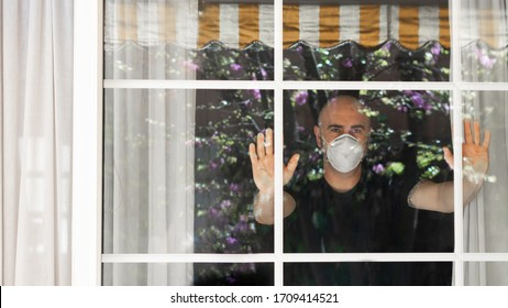 Adult man wtih a mask protection looking through the window.