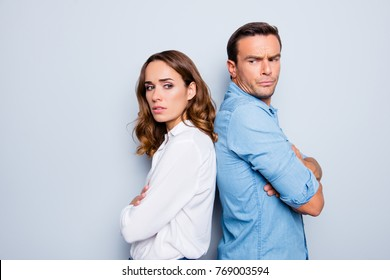 Adult mature sad, upset couple in shirts, casual outfit having family conflict, standing back to back with crossed arms ignoring each other over grey background