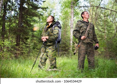 Adult men in the form of camouflage with backpacks on their shoulders follow the path in the sunny forest. Foresters inspect the park in the Siberian taiga.