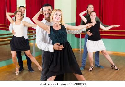 adult  men and women enjoying of tango in class