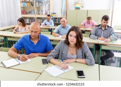 Adult men and women take a written exam in the classroom