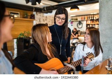 Adult mileninal women playing guitar at cafe or restaurant having fun celebrating - friendship and bonding real people concept - group of Female caucasian friends having fun happy people singing