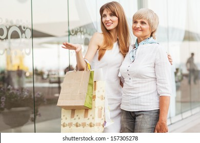 Adult mother and daughter after shopping on the background of the large glass windows.