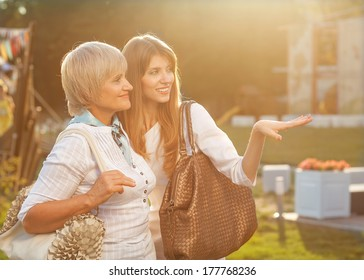 Adult mother and daughter after shopping walk down the street and talk