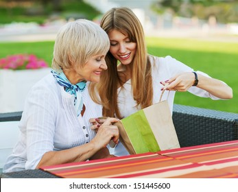 Adult mother and daughter are considering buying after shopping. They are sitting in a cafe outside.
