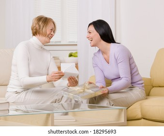 Adult mother and daughter laughing over greeting card and gift in livingroom