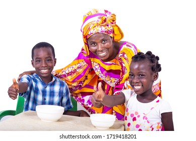 adult mother and grandchildren sitting at table showing thumbs up and smiling at camera