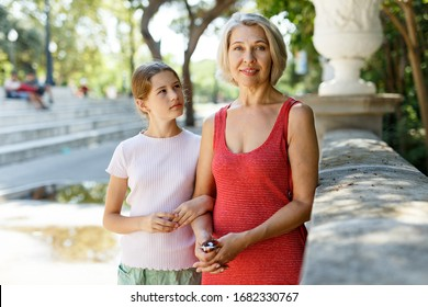 Adult mother and teen girl walking in city park at sunny day